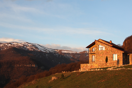 lonely stone house on the hill on the background of snowy mountains, at sunrise, horizontal, Armenia