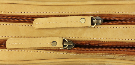 pair of zippers on the yellow leather bag, top view, one behind