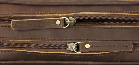 pair of zippers on the brown leather bag, top view