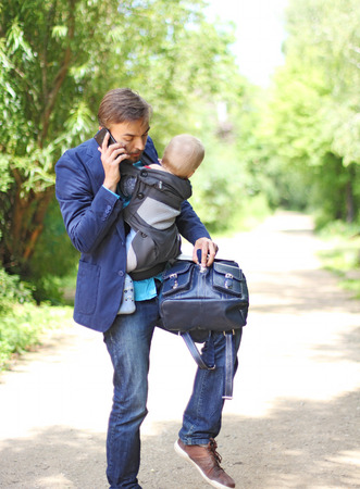 businessman with his son in a sling talks on the smartphone and try to opens up a backpack with documents