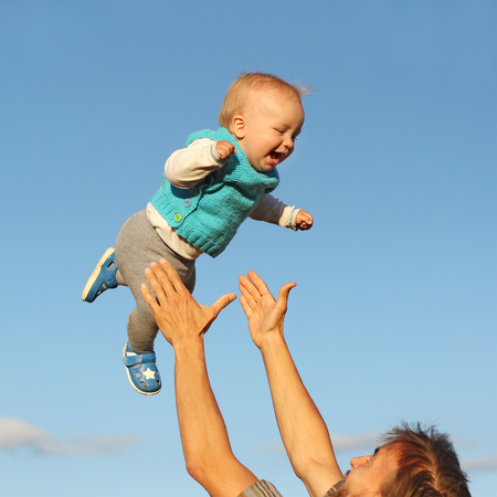 father catches his son, flying in the sky, throws and catches, square photo Reklamní fotografie