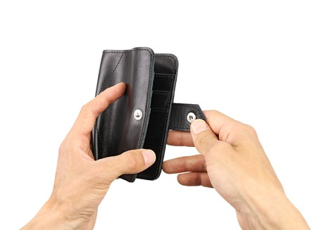 human hands unbuttons a black leather wallet, isolated background