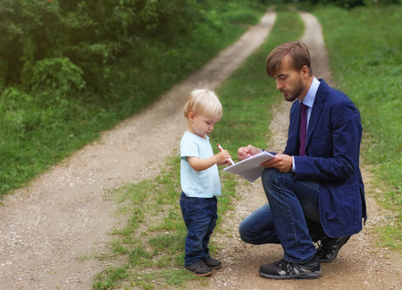 father gives documents to his son, baby writes something on papers or business contract, financial consultant explains deal to child