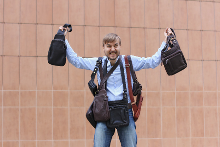 bearded man happy with the purchase of many leather bags, bags on shoulders and in hands,