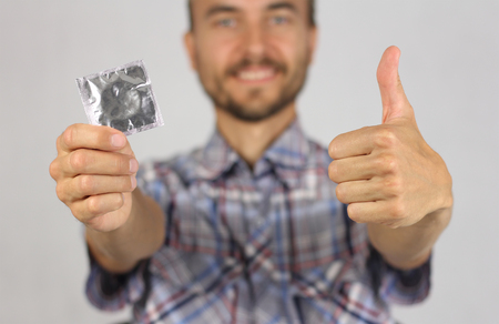 man in plaid shirt holds a new condom in hand, make gesture thumb up, joy and anticipation of pleasure, proper attitude to protection, gray background