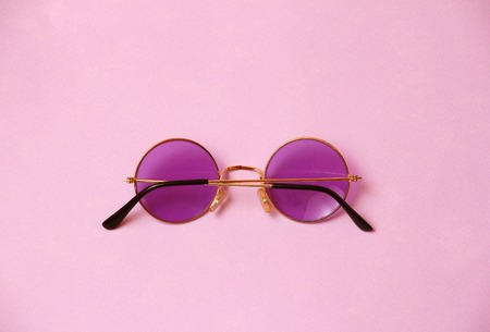 single transparent round pink purple glasses on uniform coral background, temple arm of eyeglasses are closed, back view, closeup