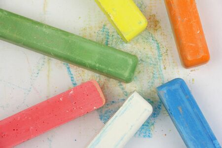 colored children crayons scattered on white paper, different colors for school or preschool activities, top view Фото со стока