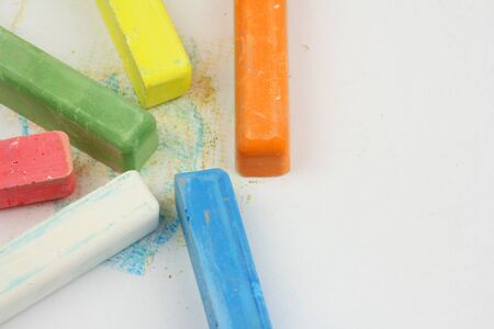 six colored children crayons scattered on white paper, different colors for school activities