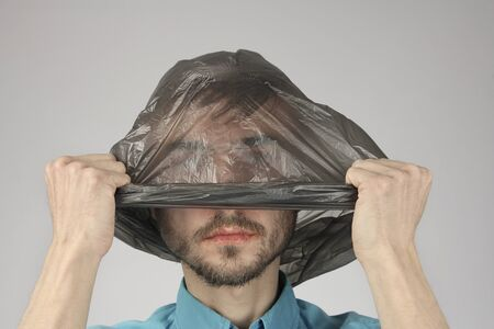 sickly man with cracked lips removes or puts black plastic bag from his head, gray background, concept big ecology problem pollution