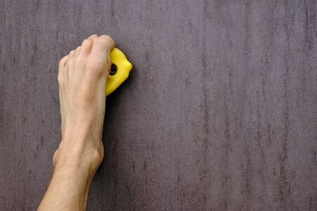 human left barefoot like a hand holds on yellow climbing hold on artificial climbing wall, concept of fun and joy sport, close-up copy space Stock Photo