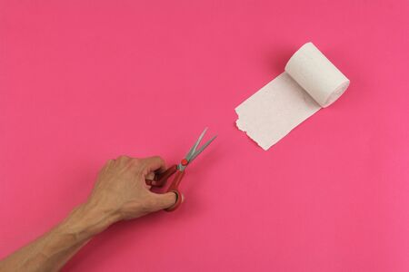 rough recycled white toilet paper on pink background and human hand with scissors, close-up, copy space, concept of stomach problems or cutting off parts Stock Photo