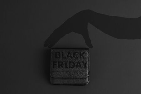 black wallet with text about black friday and dark shadow of hand, flat lay on black background, concept of special discount offer