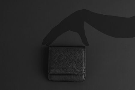 black wallet and dark shadow of hand hold it, flat lay on black background, copy space for text, concept of black friday or season special discount offer Zdjęcie Seryjne