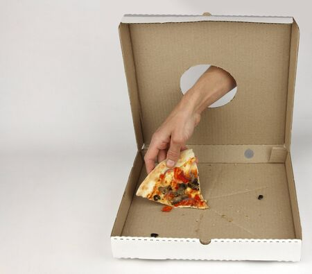 human hand through hole in cardboard box takes last piece of pizza, white background, fastfood consumption concept