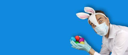 man in easter bunny and medical mask hold colored eggs, holidays in quarantine, virus or coronavirus protection and prevention, preparation for party, banner with copy space on blue background