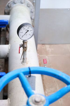 gauge sensor or pressure indicator manometer on water pipe with faucet, industrial interior in water treatment facilities