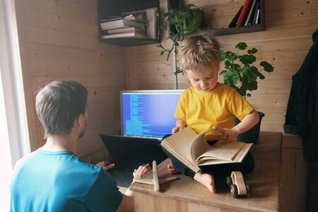 father developer freelancer work from home, child sits near and leafing through book, concept of self-isolated lifestyle workspace workplace, parenthood home office 版權商用圖片