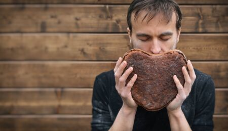 baker with love holds, smell and enjoys aroma of handmade freshly baked vegan rye whole grain sourdough bread in shape of heart, valentine gift, brown banner with copy space Stockfoto