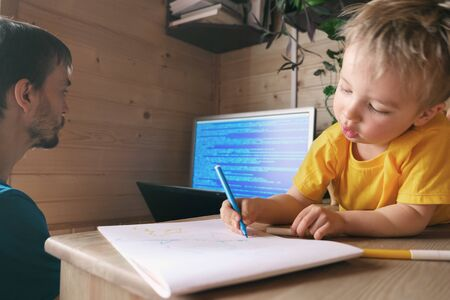 father freelancer developer working from home in quarantine, son child lying near and draws, concept of self-isolated lifestyle workspace workplace, parenthood multitasking 免版税图像