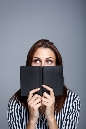 Young Woman Thinking Behind Her Black Diary  photo