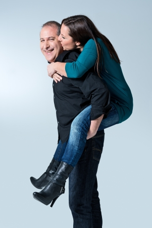 Happy young man giving a piggyback ride to her wife against white background photo