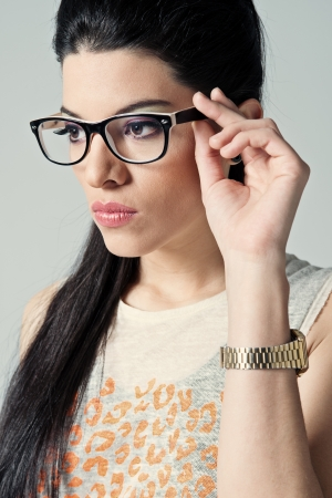 woman wearing glasses: Beautiful Girl with Black Glasses in a Grey Background