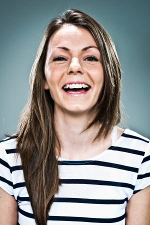 Young Woman Smiling over a Grey Background Stock Photo - 18443529