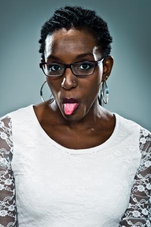sacar la lengua: Joven Mujer Feliz Negro Sacar la lengua sobre un fondo gris