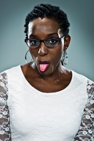 sticking out tongue: Young Happy Black Woman Sticking Out Her Tongue Over a Grey Background Stock Photo