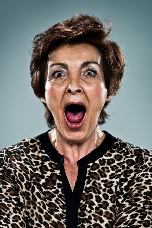 Mature Woman Shouting Over a Grey Background Stock Photo - 18443520