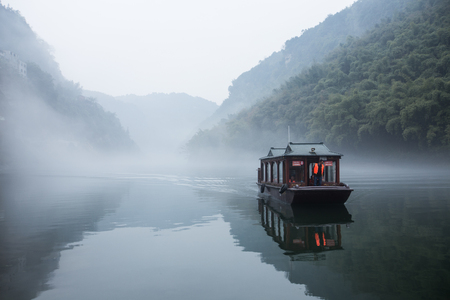 olden day: Traditional chinese tourist ferry cruising the foggy waters