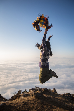 Woman doing a jump pose on the mountain