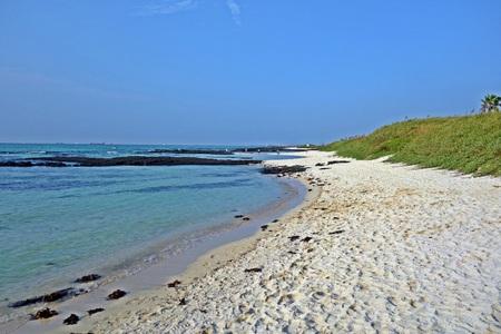 a white sandy beach and an emerald sea water of geumneung beach,jeju island,korea