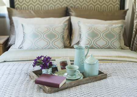 Decorative tray with book,tea set and flower on the bed photo