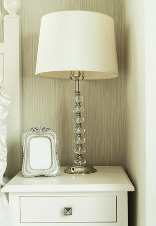 'bedside table': Bedside table with lamp, and picture frame Stock Photo