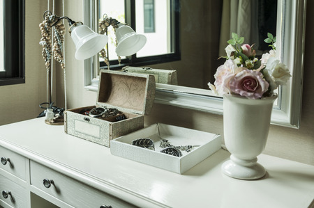 Beauty and make-up concept: mirror,lamp,jewelry and makeup box on a table photo