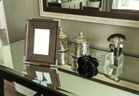Beauty and make-up concept: picture frame, jewelry and makeup brushes on a table