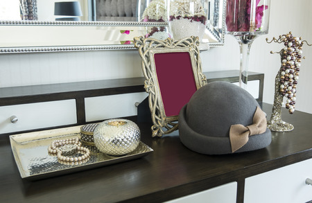 Picture frame and jewelry set on a dresser table in a contemporary room. photo