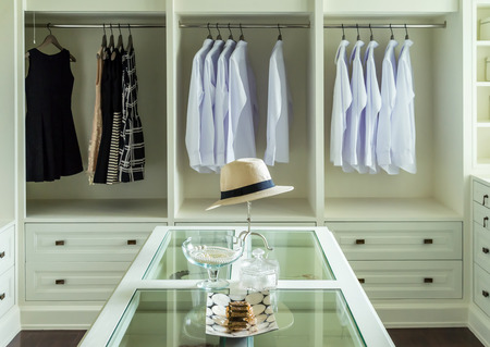 closet: white hat and jewelry set on a dresser table in a walk in closet room.