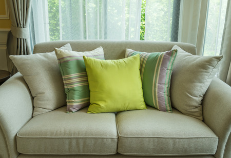 green pillows on modern sofa in living room photo