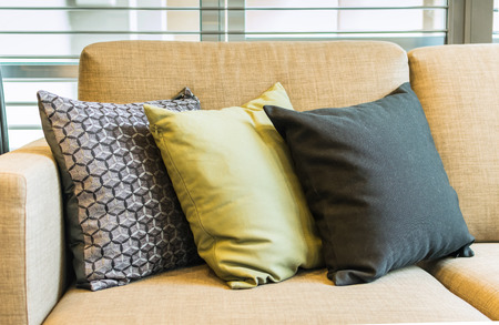 green sofa: row of pillows on sofa in living room