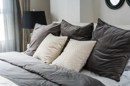 white and grey pillows on bed in modern bedroom photo