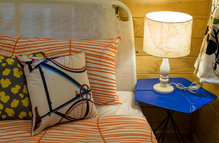 colorful pillows on bed with white lamp photo