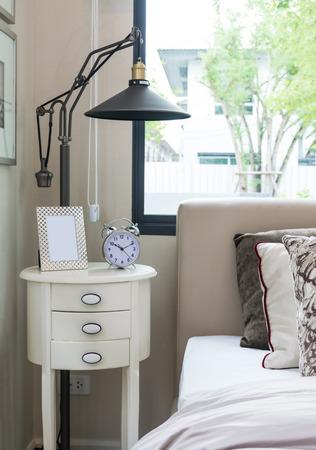 bedside: black lamp, picture frame and alarm clock on bedside table