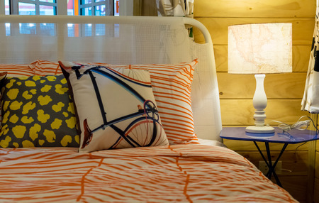 matress: colorful pillows on bed with white lamp