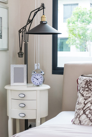 bedside lamp: black lamp, picture frame and alarm clock on bedside table