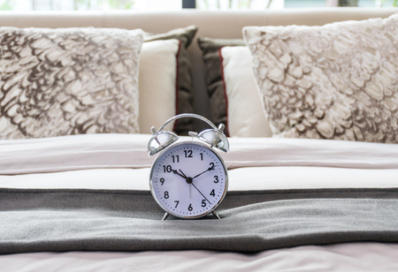 undone: classical alarm clock on bed