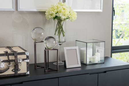 bedside lamp: Picture frame and candle lamp on a table in a contemporary room