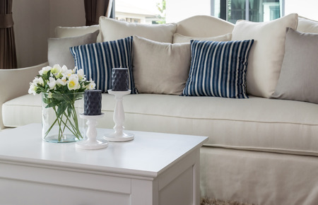 modern living room with glass vase and row of pillows on sofa Standard-Bild