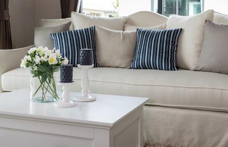moderne Wohnzimmer mit Glasvase und Reihe von Kissen auf dem Sofa